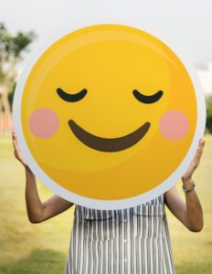 photo of a woman holding smiley face emoji in front of her face